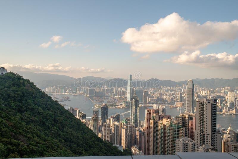 从峰顶的香港,蓝天覆盖与小山阴影的都市风景 免版税库存图片