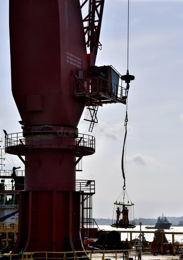 从工作驳船的近海工作者调动使用起重机 库存图片