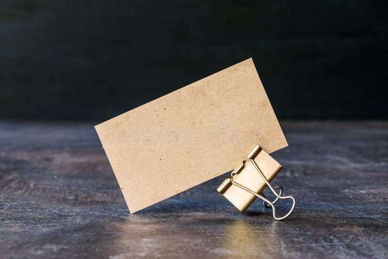 从工艺的名片回收了与金属黏合剂夹子的纸在桌上 纸板在黑暗的背景的名片 库存照片