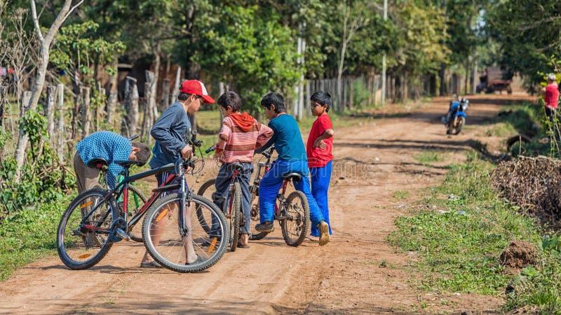从巴拉圭的五个小人有他们的在其中一条的自行车的典型的巴拉圭含沙道路 免版税图库摄影