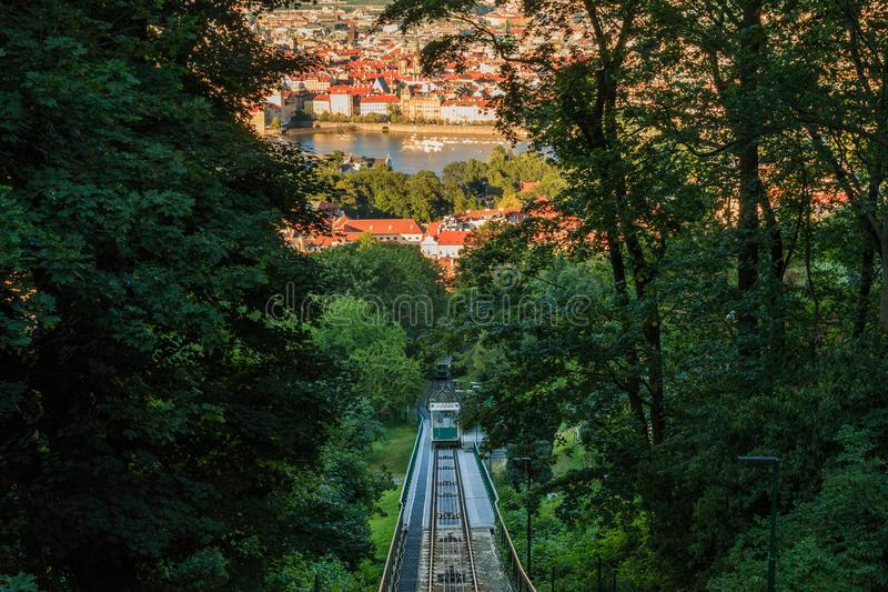 从布拉格的佩特林山欣赏索道缆车,阳光下树木,背景中是伏尔塔瓦河 免版税库存照片