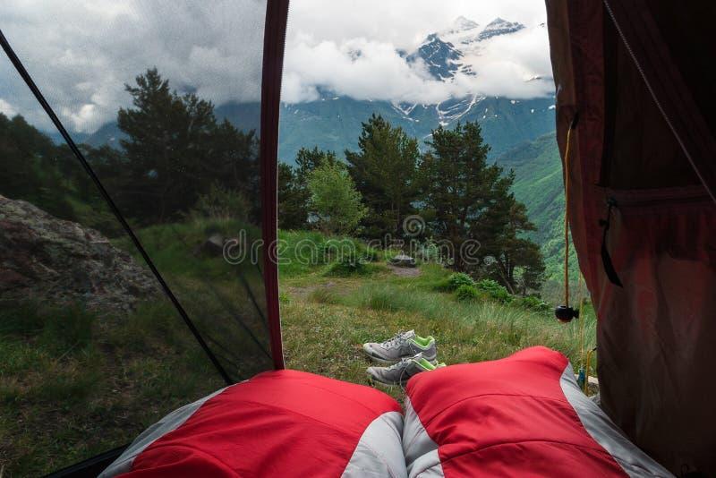 从帐篷的看法到白种人土坎 两个红色睡袋在帐篷在 库存图片