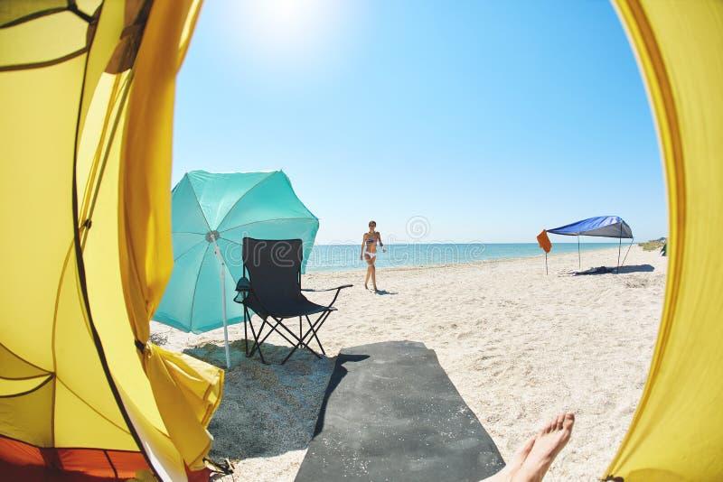 从帐篷里边的看法在沙滩和海在一个明亮的晴天 图库摄影