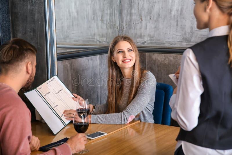 从年轻夫妇的女服务员采取和定货在餐馆 库存照片