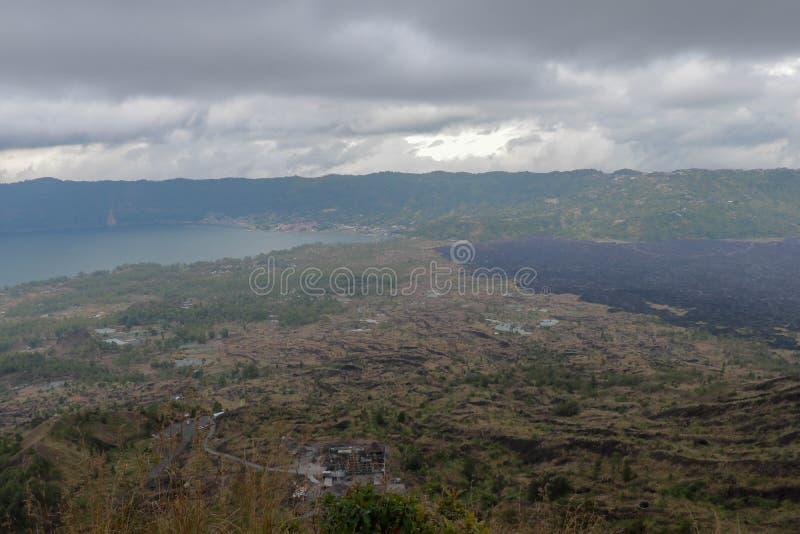 从庄严Gunung Batur山的看法到与湖和黑熔岩荒野的火山的破火山口 与黑暗多云的阴暗天空 免版税库存图片
