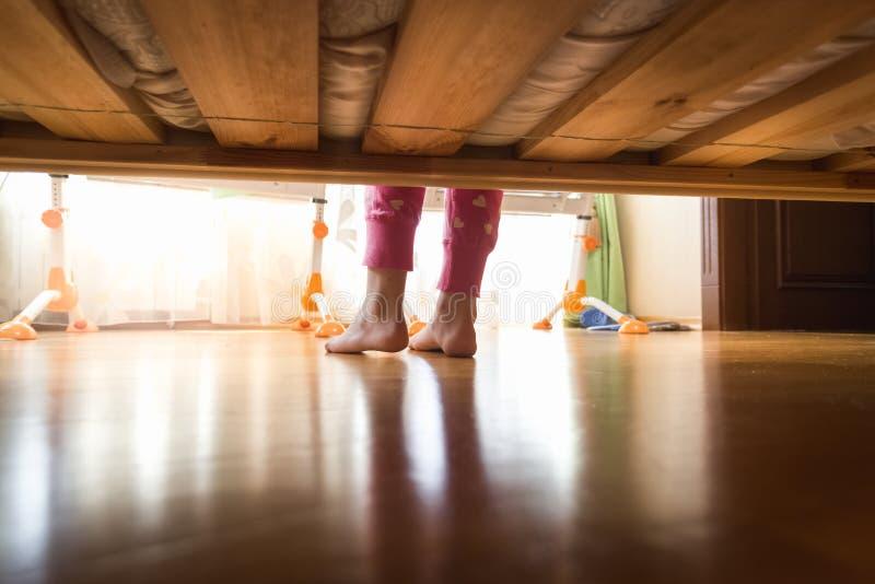 从床下面的看法在木地板上的十几岁的女孩脚 图库摄影