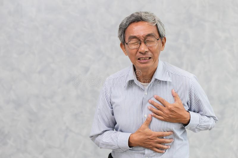 从心脏病发作手盖子胸口的老人油漆 库存照片