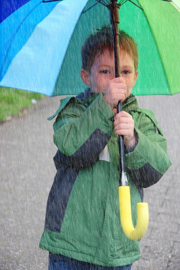 从恶劣天气保护,有大伞的男孩 库存照片
