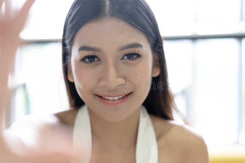 从手的特写镜头年轻亚洲妇女作为selfie有电话的在她的办公室 概念愉快女商人的生活方式 库存照片