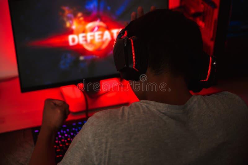 从打在com的年轻游戏玩家人后面的画象电子游戏 库存照片