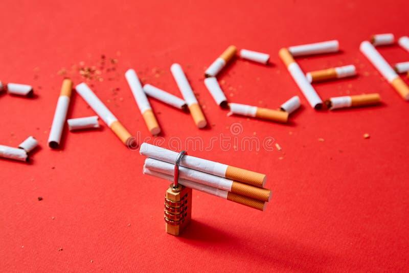 从抽烟的缓慢的死亡,停止烟和战斗与癌症概念 在题字癌症的背景的锁 库存照片