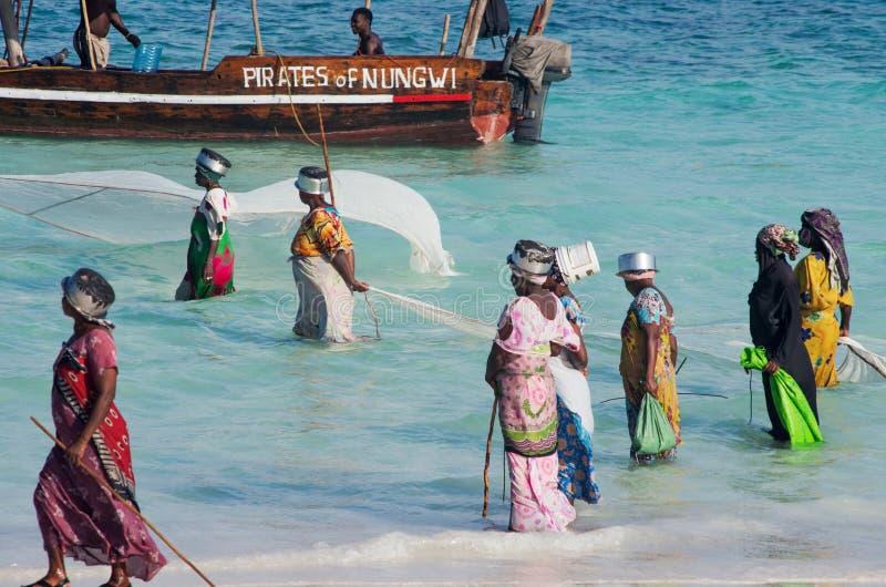 从捉住小鱼网的渔村的非洲妇女在海洋 免版税库存照片