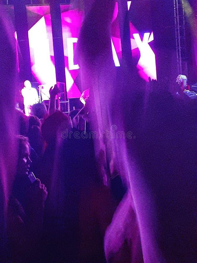 从摇滚乐队音乐会的霓虹照片在正方形 免版税库存图片
