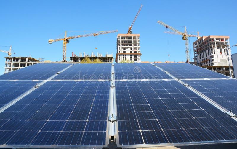 从收获与起重机的太阳能电池的绿色能量太阳光在建造场所背景作为现代全球性建筑 免版税库存照片