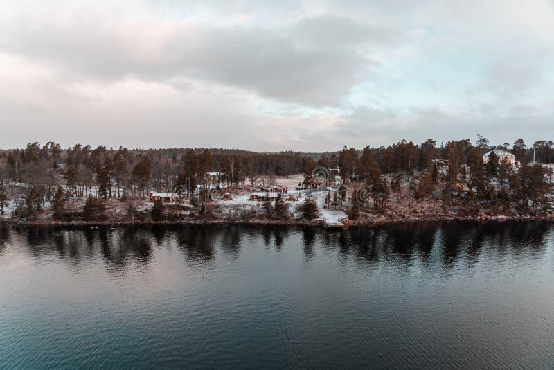从斯德哥尔摩群岛的看法有在地面上的雪的与房子在森林 库存照片