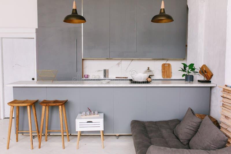 从新的顶楼公寓,灰色家具演播室厨房的看法  免版税库存图片