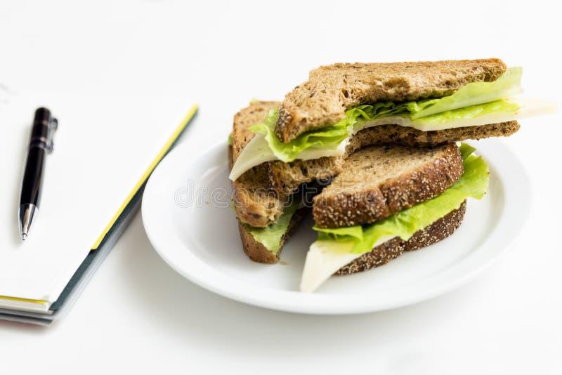 从新鲜的多士的三明治用乳酪和沙拉在工作地点 W 免版税库存图片