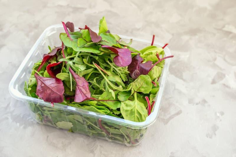 从新鲜的有机沙拉的混合在塑料透明包装在一张木桌上 复制空间 库存图片