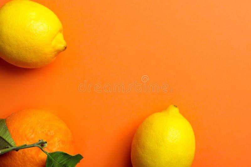 从新鲜的未加工的柑橘水果柠檬的框架构成橙色在与绿色叶子的词根 健康生活方式维生素戒毒所 免版税库存照片