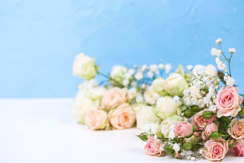 从新鲜的白色gypsofila的边界和白色玫瑰色花反对蓝色织地不很细背景 免版税库存图片