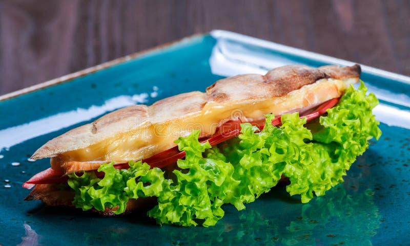 从新鲜的皮塔饼面包的三明治用莴苣,切片新鲜的蕃茄,火腿猪肉和乳酪在黑暗的木背景 免版税库存照片