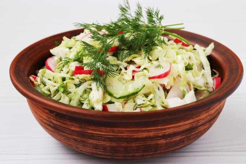 从新鲜蔬菜的沙拉:圆白菜、萝卜、黄瓜、葱和莳萝,在一个棕色色拉盘 免版税库存照片
