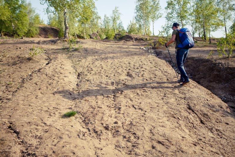 从旅游人后面的照片有去的拐杖的小山 库存图片