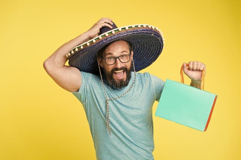 从旅行的购买纪念品 男服阔边帽帽子购物的黄色背景 有胡子的人愉快在阔边帽 r 库存照片