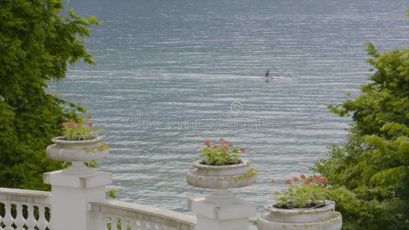 从旅馆大阳台的湖视图在夏天 r 通过他的Summer湖与皮船的人 免版税库存照片