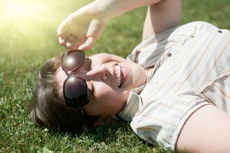 从明亮的太阳的妇女半眯着的眼睛,在绿草,城市公园,室外的夏天的谎言 免版税库存照片