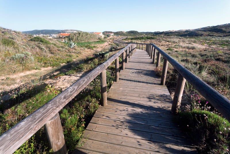 从晴朗的海滩的木道路到村庄通过农村风景,葡萄牙 青山在平安的自然区域 免版税库存照片
