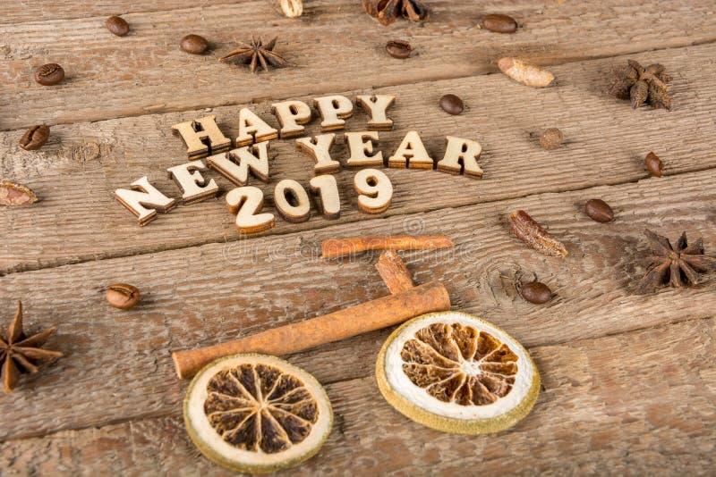 从木信件和数字'新年快乐'一辆自行车和一棵树的题字从香料在粗砺的木头背景  免版税库存照片