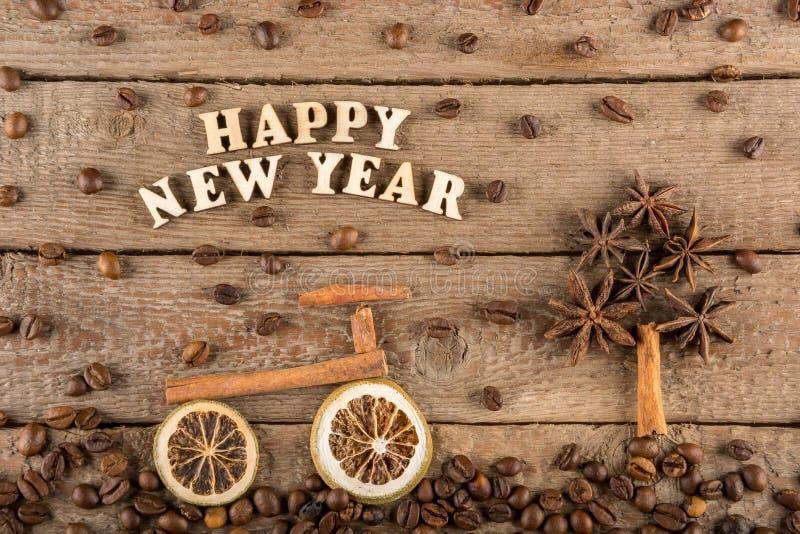 从木信件和数字'新年快乐'一辆自行车和一棵树的题字从香料在粗砺的木头背景  免版税图库摄影