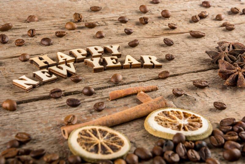 从木信件和数字'新年快乐'一辆自行车和一棵树的题字从香料在粗砺的木头背景  库存照片