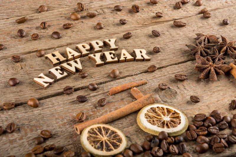 从木信件和数字'新年快乐'一辆自行车和一棵树的题字从香料在粗砺的木头背景  免版税库存图片