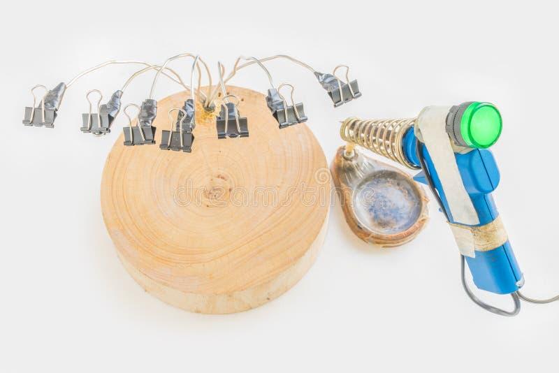 从木切板、折叠后面夹子有电焊铁的和立场的DIY多用途钳位在白色 免版税库存照片