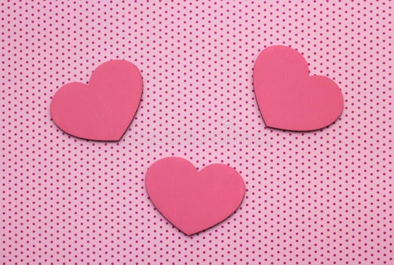 从木头的桃红色圆点背景和心脏 免版税库存图片