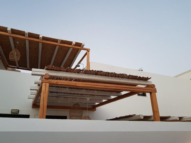 从木棚子下面射击在白色大厦附近墙壁的在小镇街道上的反对无云的天空蔚蓝的 免版税库存照片