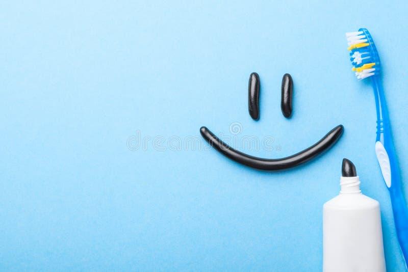 从木炭的黑牙膏白色牙的 以微笑的形式牙膏在面孔、管和牙刷在蓝色 图库摄影