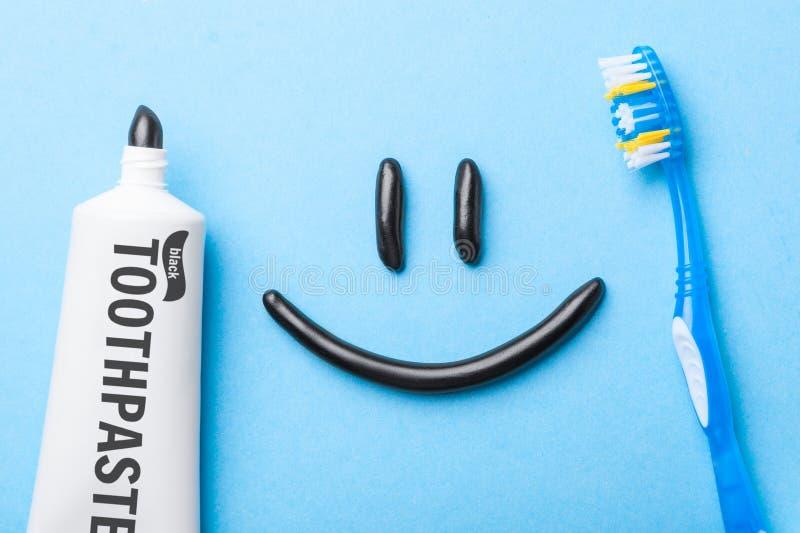 从木炭的黑牙膏白色牙的 以微笑的形式牙膏在面孔、管和牙刷在蓝色 免版税库存图片