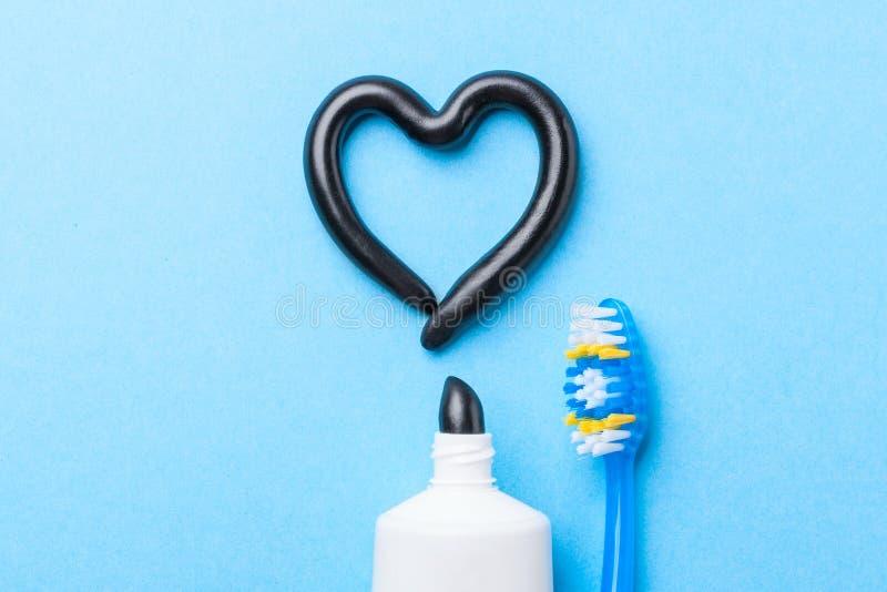 从木炭的黑牙膏白色牙的 以心脏、管和牙刷的形式牙膏在蓝色 免版税库存图片