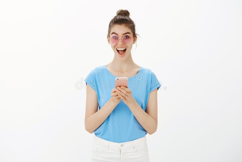 从未是那么愉快的接受消息 时髦的太阳镜的愉快的少妇,广泛地微笑和注视快乐在 免版税库存图片