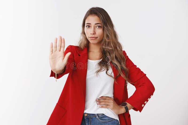 从未没有手段 穿红色夹克的画象失望的无印记的确信的年轻25s白种人卷发的妇女 库存图片