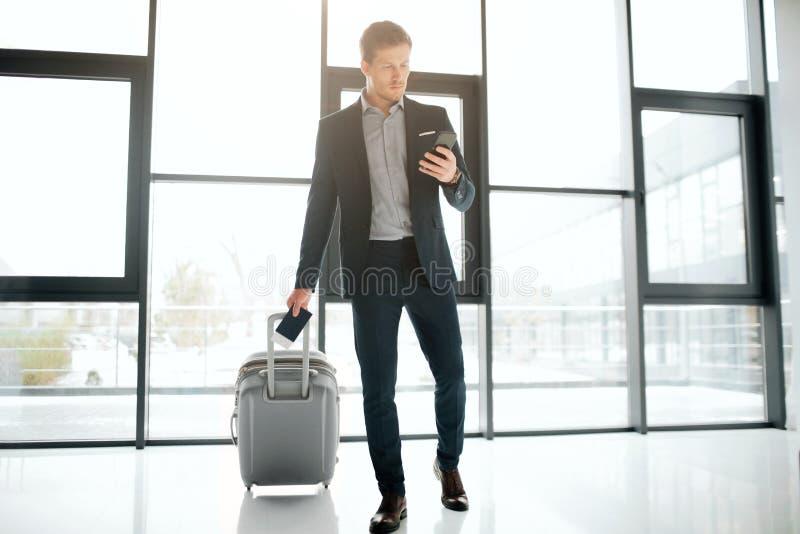 从机场窗口的严肃的年轻商人步行今后 他滚动suitcaase并且在手中拿着黑电话 人神色 免版税库存图片