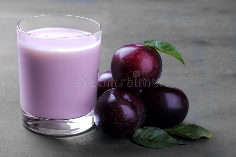 从李子和新鲜的成熟李子的酸奶与在灰色背景的叶子 免版税库存图片
