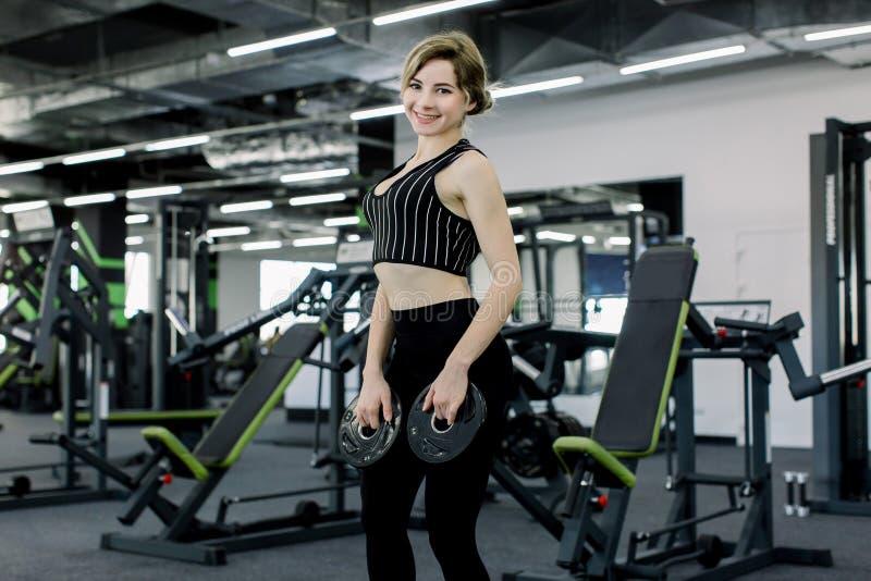 从杠铃的运动年轻女人藏品圆盘和行使在健身房 免版税库存图片