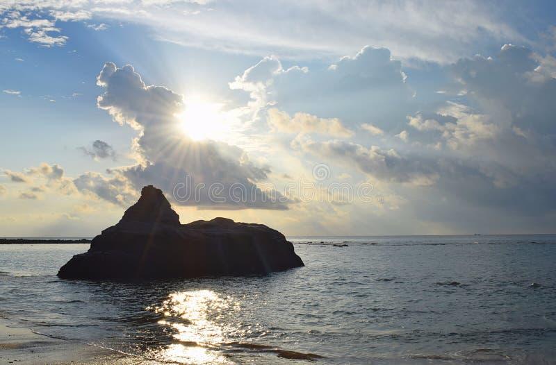 从来通过在晴朗的天空的云彩的金黄太阳的明亮的阳光在海水和岩石 免版税库存图片