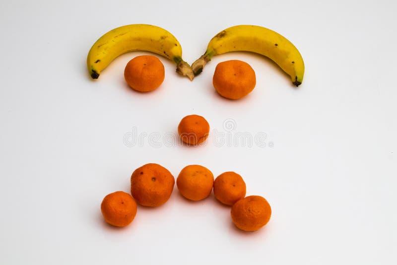 从果子的面孔在白色背景 面孔做了用新鲜水果 香蕉,普通话蜜桔 免版税库存照片
