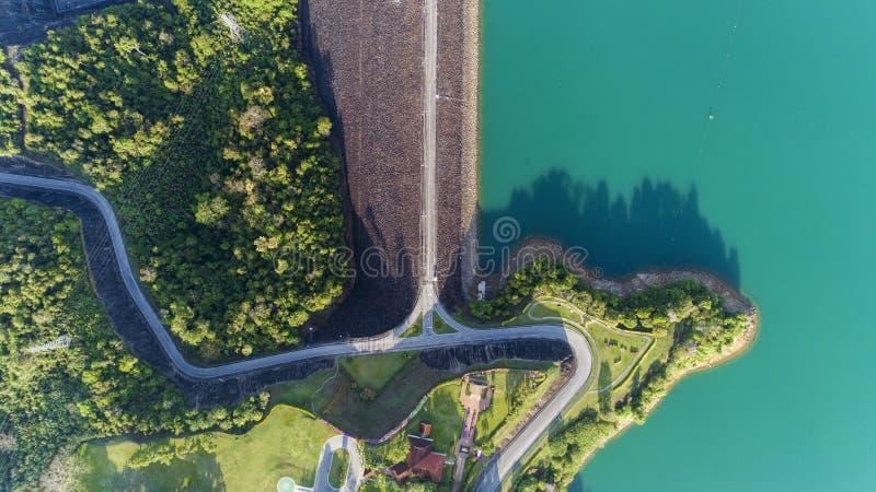 从柏油路,美好的自然风景飞行的寄生虫的空中照片在水坝附近的 图库摄影