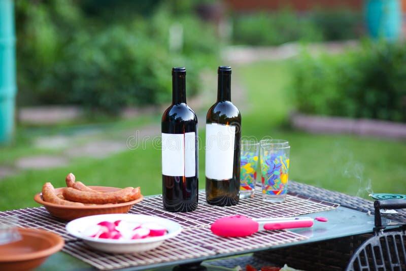 从格栅谎言的水多的可口香肠在一张柳条桌上的一块板材以绿草为背景 在两个瓶附近 库存图片